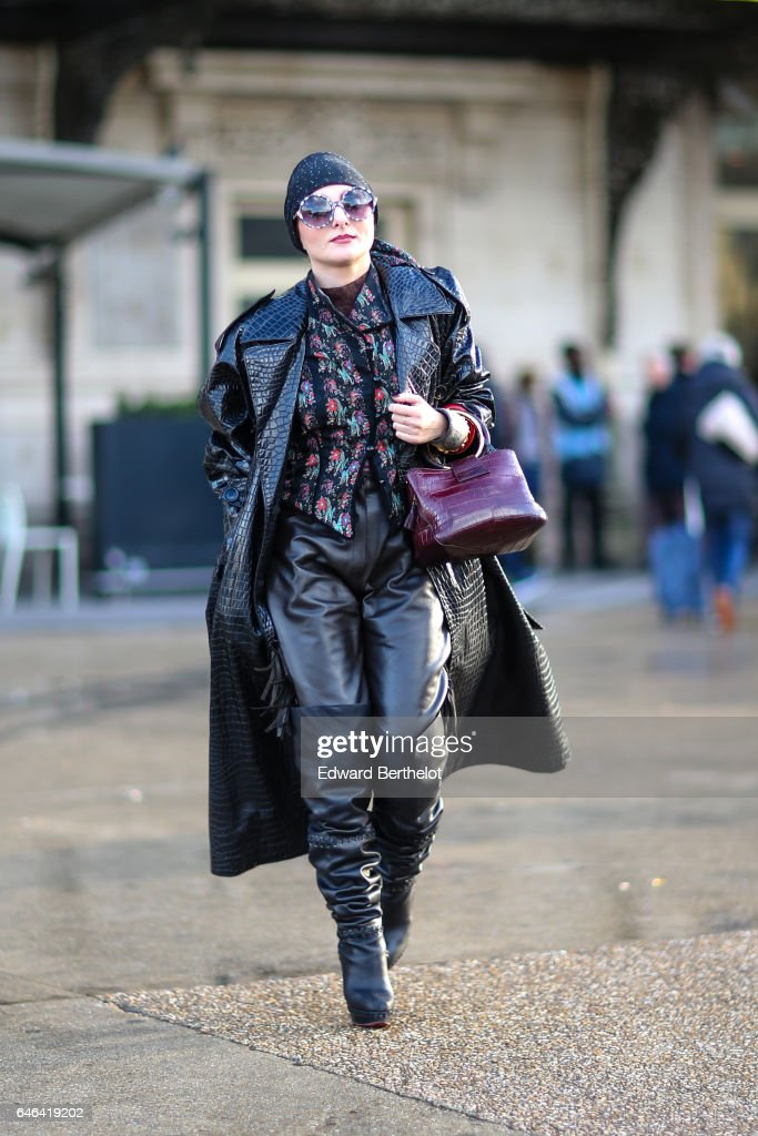 A guest wears a beanie hat, sunglasses, a black long coat, a purple bag, a floral print shirt, black leather pants, and boots, outside the Olivier Theyskens show, during Paris Fashion Week Womenswear Fall/Winter 2017/2018, on February 28, 2017 in Paris, France.