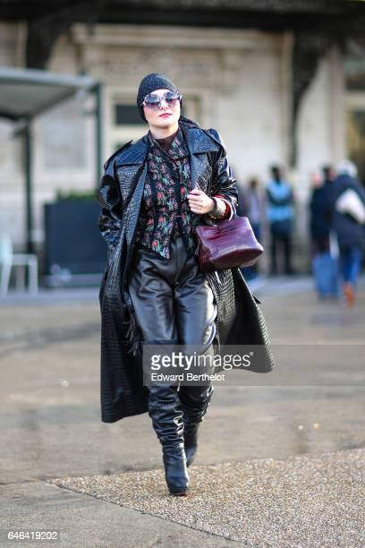 A guest wears a beanie hat sunglasses a black long coat a purple bag a floral print shirt black leather pants and boots outside the Olivier Theyskens...