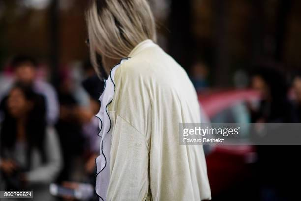 A guest wears a beige and white flounced jacket outside Lanvin during Paris Fashion Week Womenswear Spring/Summer 2018 on September 27 2017 in Paris...