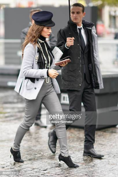 A guest wears a beret hat a gray jacket gray pants black heels shoes and attends Le Defile L'Oreal Paris as part of Paris Fashion Week Womenswear...
