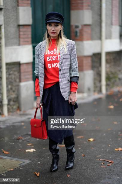A guest wears a beret hat a tartan blazer jacket a red pull over a skirt black boots a red bag outside Valentino during Paris Fashion Week Womenswear...