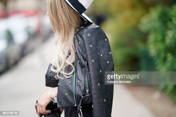 A guest wears a black and white hat a black leather studded jacket outside Lanvin during Paris Fashion Week Womenswear Spring/Summer 2018 on...
