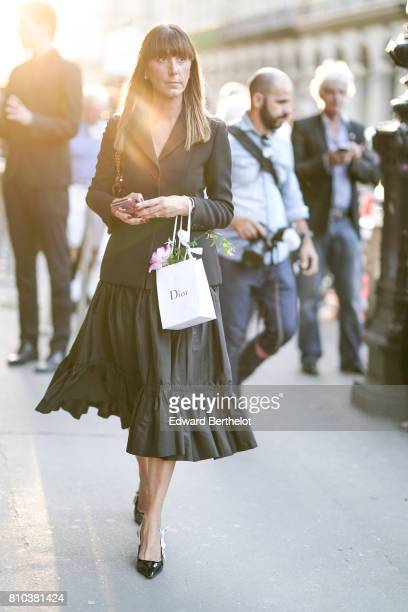 A guest wears a black blazer jacket a black ruffled skirt black heels shoes outside the 'Christian Dior couturier du reve' Exhibition Launch...