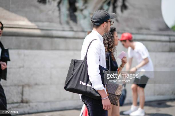 A guest wears a black cap and a vuitton bag outside the Icosae show during Paris Fashion Week Menswear Spring/Summer 2018 on June 21 2017 in Paris...