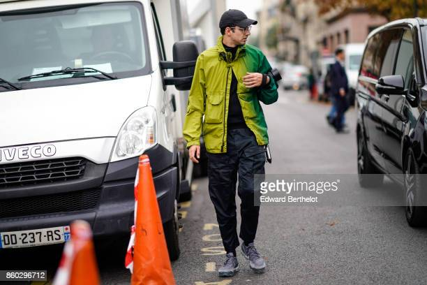 A guest wears a black cap hat a jacket in shades of green black pants with pockets grey sneakers outside Lanvin during Paris Fashion Week Womenswear...