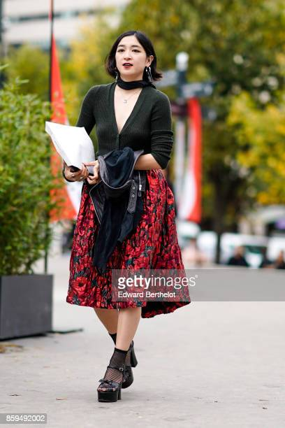 A guest wears a black cardigan large flower print skirt black fishnet socks and black wedge shoes outside Ann Demeulemeester during Paris Fashion...
