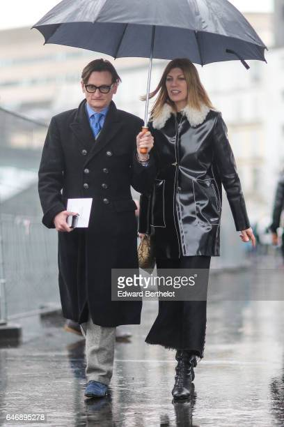 A guest wears a black coat another guest wears a black vinyl coat with white fur outside the Dries Van Noten show during Paris Fashion Week...