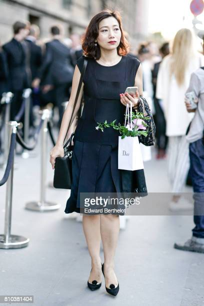A guest wears a black dress and black heels shoes outside the 'Christian Dior couturier du reve' Exhibition Launch celebrating 70 years of creation...
