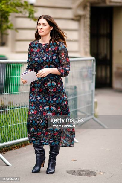 A guest wears a black dress with green and red floral prints black boots outside Lanvin during Paris Fashion Week Womenswear Spring/Summer 2018 on...