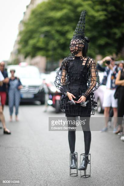 A guest wears a black full outfit covered by a black grid outside the Dior show during Paris Fashion Week Menswear Spring/Summer 2018 on June 24 2017...