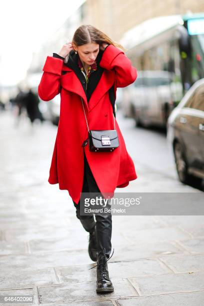 A guest wears a black Furla bag a red coat black pants and black boots outside the JOUR/NE show during Paris Fashion Week Womenswear Fall/Winter...