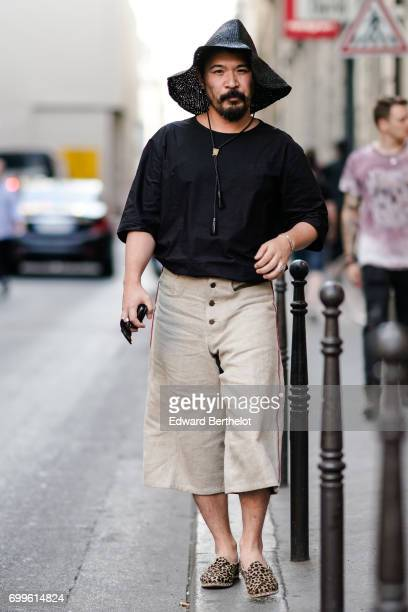 A guest wears a black hat a black top and cropped pants outside the OAMC show during Paris Fashion Week Menswear Spring/Summer 2018 on June 21 2017...