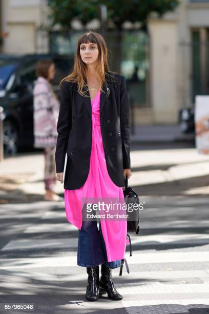 A guest wears a black jacket a pink dress over flare jeans black shoes outside Miu Miu during Paris Fashion Week Womenswear Spring/Summer 2018 on...