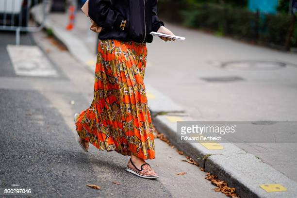 A guest wears a black jacket an orange and yellow ethnical pattern pleated skirt light brown print shoes outside Lanvin during Paris Fashion Week...