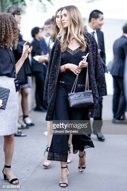 A guest wears a black lace outfit a black leather crocodile bag outside the launch party for Chanel's new perfume 'Gabrielle' during Paris Fashion...