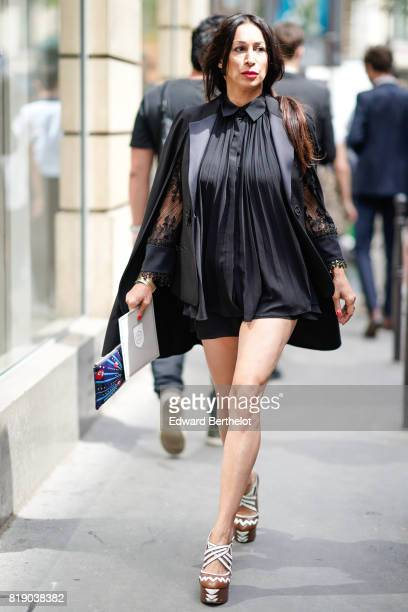 A guest wears a black short dress outside the Elie Saab show during Paris Fashion Week Haute Couture Fall/Winter 20172018 on July 5 2017 in Paris...