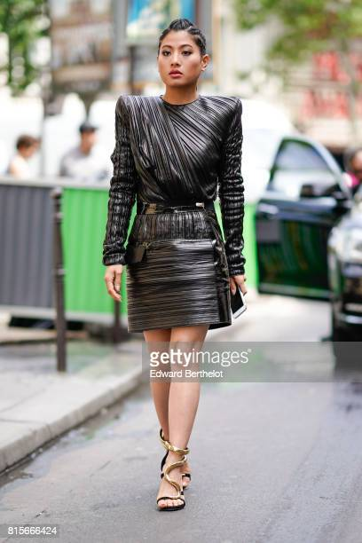 A guest wears a black shoulder pad leather pattern dress heels shoes with snake shaped straps outside the Elie Saab show during Paris Fashion Week...
