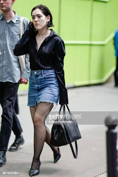 A guest wears a black silk shirt a blue denim short a black bag outside the Y3 show during Paris Fashion Week Menswear Spring/Summer 2018 on June 25...