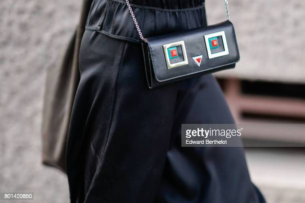 A guest wears a black silk skirt and a leather bag with colored features outside the Kenzo show during Paris Fashion Week Menswear Spring/Summer 2018...