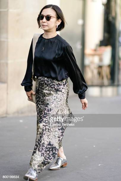 A guest wears a black silk top and a floral print skirt and silver shoes after the CDG Comme des Garcons show during Paris Fashion Week Menswear...