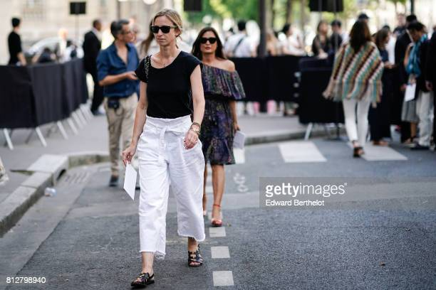 A guest wears a black tank top white large cropped pants sandals sunglasses outside the Valentino show during Paris Fashion Week Menswear...