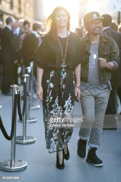 A guest wears a black top a black flower print skirt black shoes outside the 'Christian Dior couturier du reve' Exhibition Launch celebrating 70...