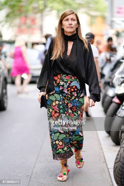 A guest wears a black top a flower print skirt gladiator sandals with colored pompoms outside the Elie Saab show during Paris Fashion Week Haute...