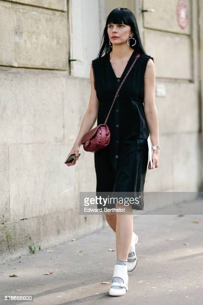 A guest wears a black vneck sleeveless button dress a purple bag gray socks white shoes outside the launch party for Chanel's new perfume 'Gabrielle'...