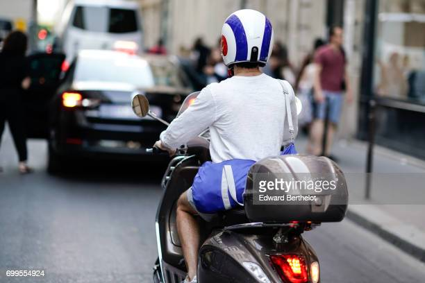 A guest wears a blue and white helmet and rides a scooter outside the OAMC show during Paris Fashion Week Menswear Spring/Summer 2018 on June 21 2017...