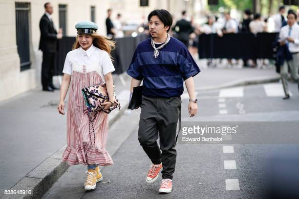 A guest wears a blue beret a white shirt a pink dress orange shoes sneakers a guest wears a blue striped tshirt gray pants pink sneakers outside the...