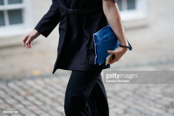 A guest wears a blue clutch outside Simone Rocha during London Fashion Week September 2017 on September 16 2017 in London England