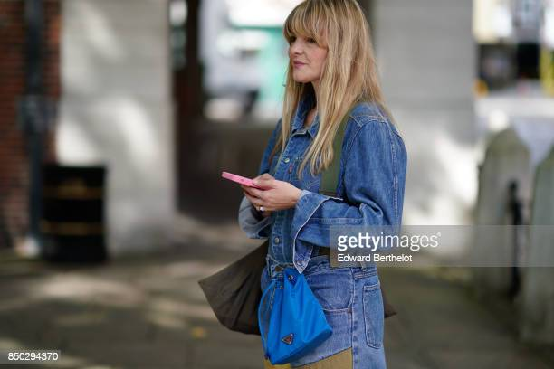 A guest wears a blue denim jacket and a blue bag outside Simone Rocha during London Fashion Week September 2017 on September 16 2017 in London England