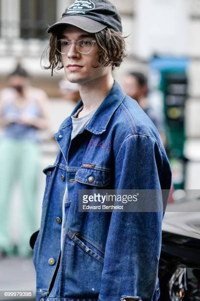 A guest wears a blue denim jacket and a cap outside the OAMC show during Paris Fashion Week Menswear Spring/Summer 2018 on June 21 2017 in Paris...