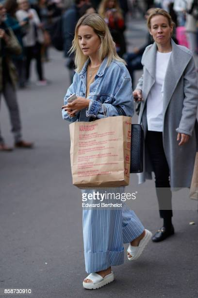 A guest wears a blue denim jacket blue striped pants white shoes outside Stella Mccartney during Paris Fashion Week Womenswear Spring/Summer 2018 on...
