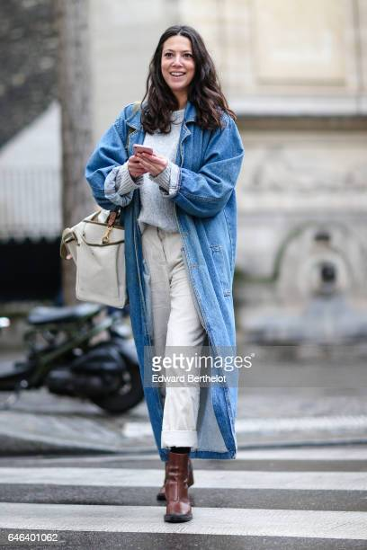 A guest wears a blue denim long jacket brown boots a white top and white pants outside the JOUR/NE show during Paris Fashion Week Womenswear...