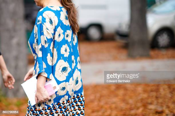 A guest wears a blue dress with white floral prints and geometric design outside Lanvin during Paris Fashion Week Womenswear Spring/Summer 2018 on...