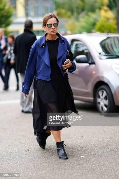 A guest wears a blue jacket a black dress black shoes mirror sunglasses outside Leonard during Paris Fashion Week Womenswear Spring/Summer 2018 on...