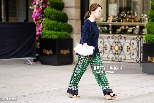 A guest wears a blue pull over a white bag green pants with embroidery espadrille shoes outside the Schiaparelli show during Paris Fashion Week Haute...