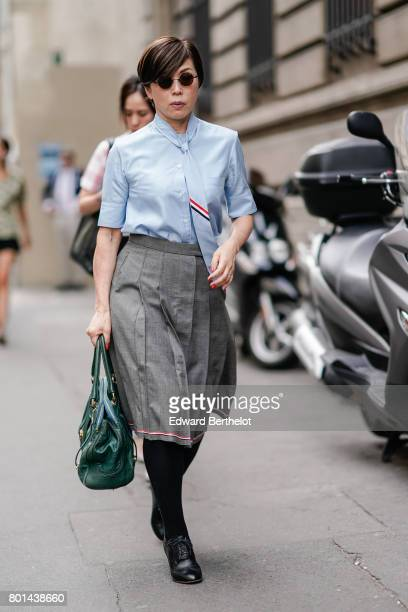 A guest wears a blue shirt a tie a gray skirt a green bag black socks black shoes outside the Thom Browne show during Paris Fashion Week Menswear...