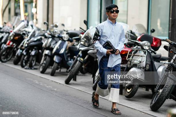 A guest wears a blue shirt sunglasses cropped pants and sandals outside the OAMC show during Paris Fashion Week Menswear Spring/Summer 2018 on June...