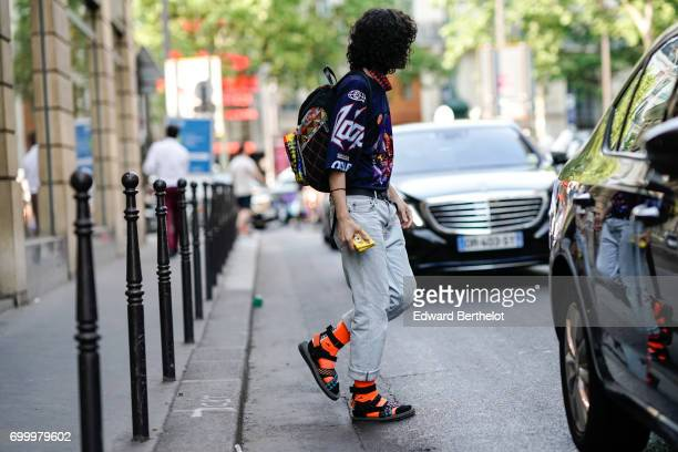 A guest wears a blue shirt with colored prints orange socks a colored backpack outside the OAMC show during Paris Fashion Week Menswear Spring/Summer...