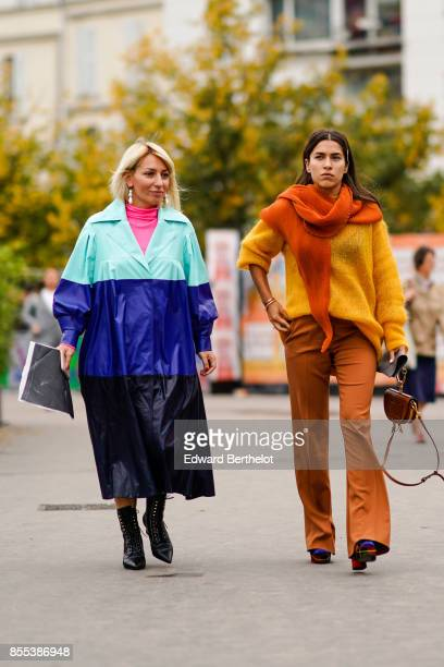 A guest wears a blue striped rain coat a guest wears an orange scarf a yellow pull over flare pants outside Ann Demeulemeester during Paris Fashion...