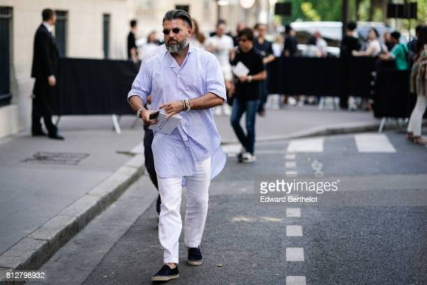 A guest wears a blue striped shirt white pants black shoes sunglasses outside the Valentino show during Paris Fashion Week Menswear Spring/Summer...