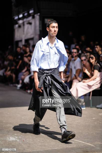 A guest wears a blue top a blue shirt gray pants outside the Y/Project show during Paris Fashion Week Menswear Spring/Summer 2018 on June 21 2017 in...