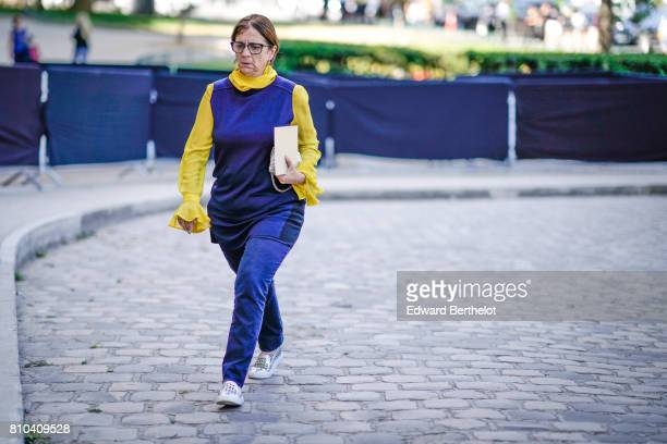 A guest wears a blue top blue pants a yellow pull over outside the Ralph Russo show during Paris Fashion Week Haute Couture Fall/Winter 20172018 on...