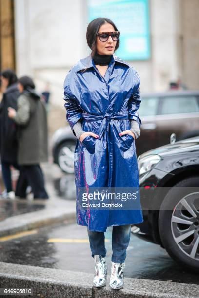 A guest wears a blue vinyl rain coat outside the Rochas show during Paris Fashion Week Womenswear Fall/Winter 2017/2018 on March 1 2017 in Paris...