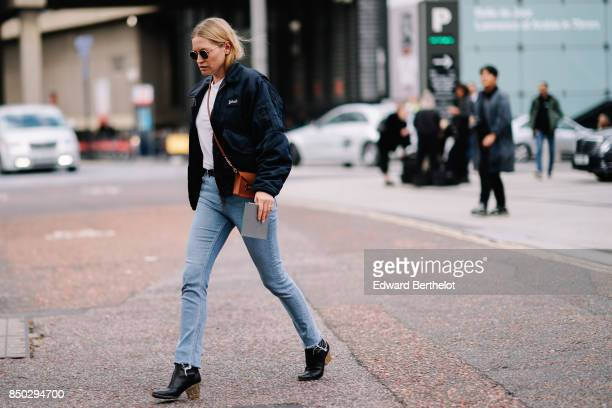 A guest wears a bomber jacket blue jeans black leather shoes a clutch during London Fashion Week September 2017 on September 17 2017 in London England