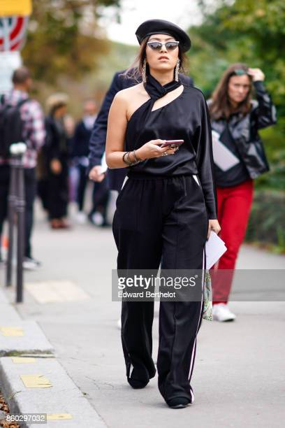 A guest wears a brown beret hat sunglasses large earrings a black scarf a black satin one shoulder top black pants with white stripe on the side...