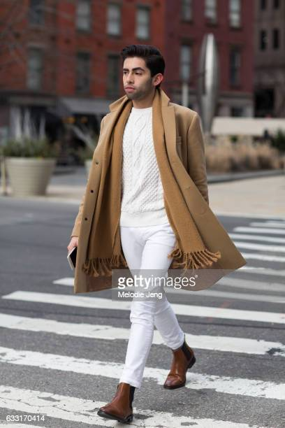 A guest wears a camel coat and scarf over a white sweater and jeans and brown leather Chelsea boots outside New York Men's Day at Dune Studios on...
