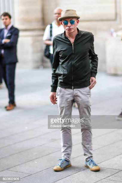 A guest wears a camel hat green sunglasses gray pants blue shoes outside the Hermes show during Paris Fashion Week Menswear Spring/Summer 2018 on...